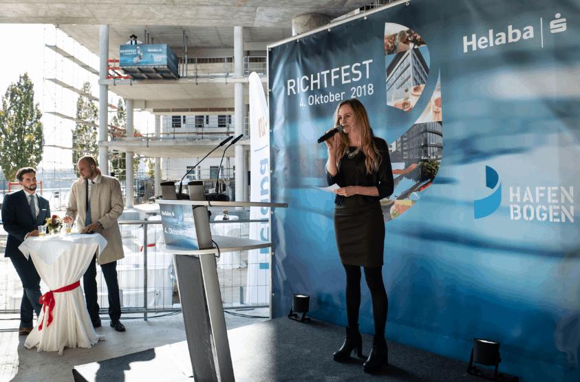 Für die KION Group AG moderierte Janina Treis das Richtfest des Bürogebäude Hafenbogen, dem abschließenden Baustein in der Gesamtbaulandentwicklung des Frankfurter Westhafen.